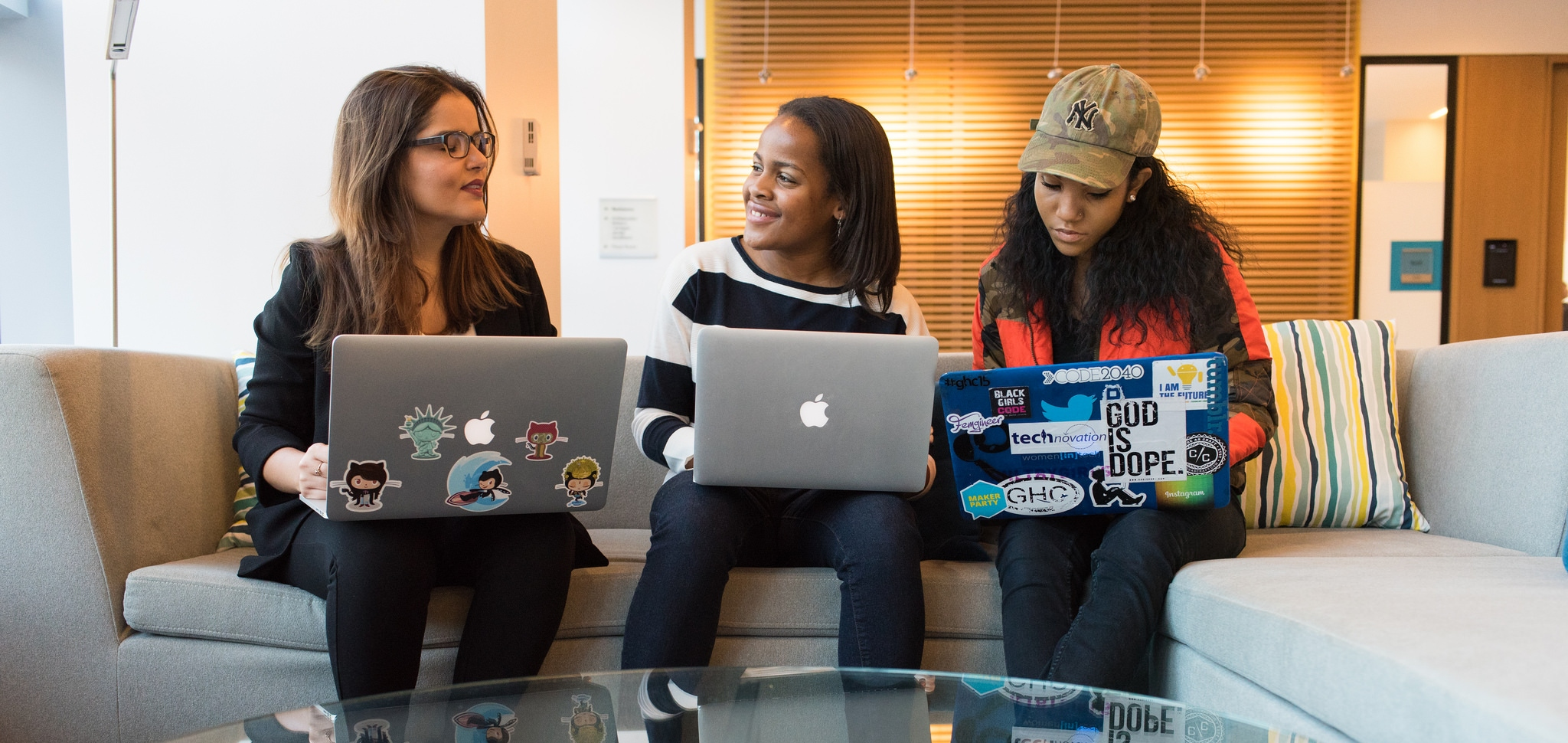 Three young women sitting on a couch with laptops in hand.