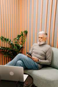 man in gray sweater sitting on gray couch