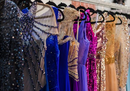 Many brilliant bright evening dresses hanging in a store