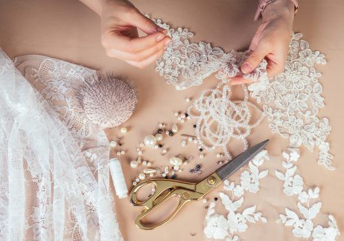 close-up hands of woman seamstress tailor ( dressmaker) designer wedding dress sews beads to lace on a blue background in the studio