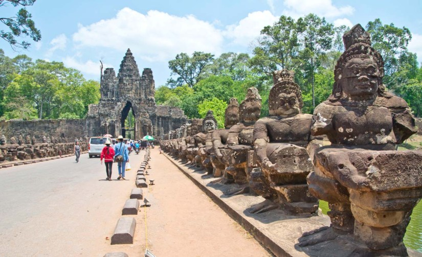 Gate to Angkor Thom gate and statues on side of road