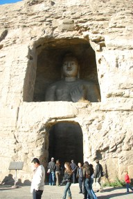 Buddha inside a cave, looking out a window.