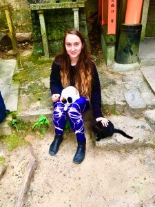 a girl sits with a black and white cat on her lap and a black cat to her left side.