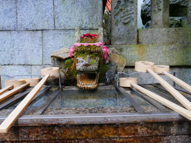 a stone dragon sitting over shrine water
