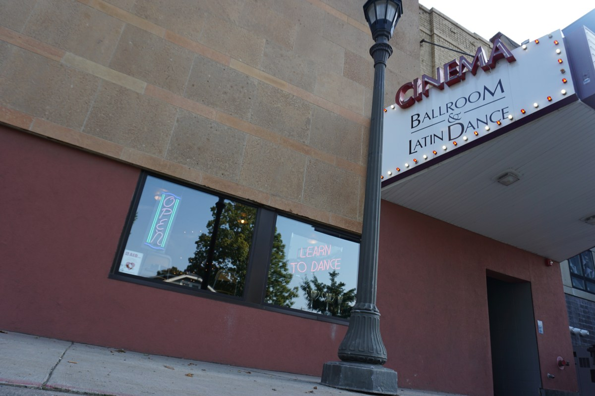 """Photograph of Cinema Ballroom in St. Paul, MN, from the outside showing large marquee with red and white light bulbs saying, """"Cinema Ballroom & Latin Dance,"""" and neon light signs in the window saying """"Learn To Dance"""" and """"Open"""""""