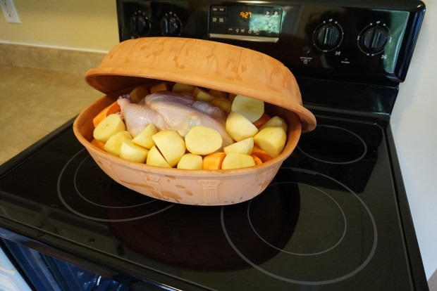 Photo of a clay cooker filled with a whole chicken and root vegetables ready to bake in the oven after closing the lid of the cooker that is shown tilted open to allow the contents to be viewed.