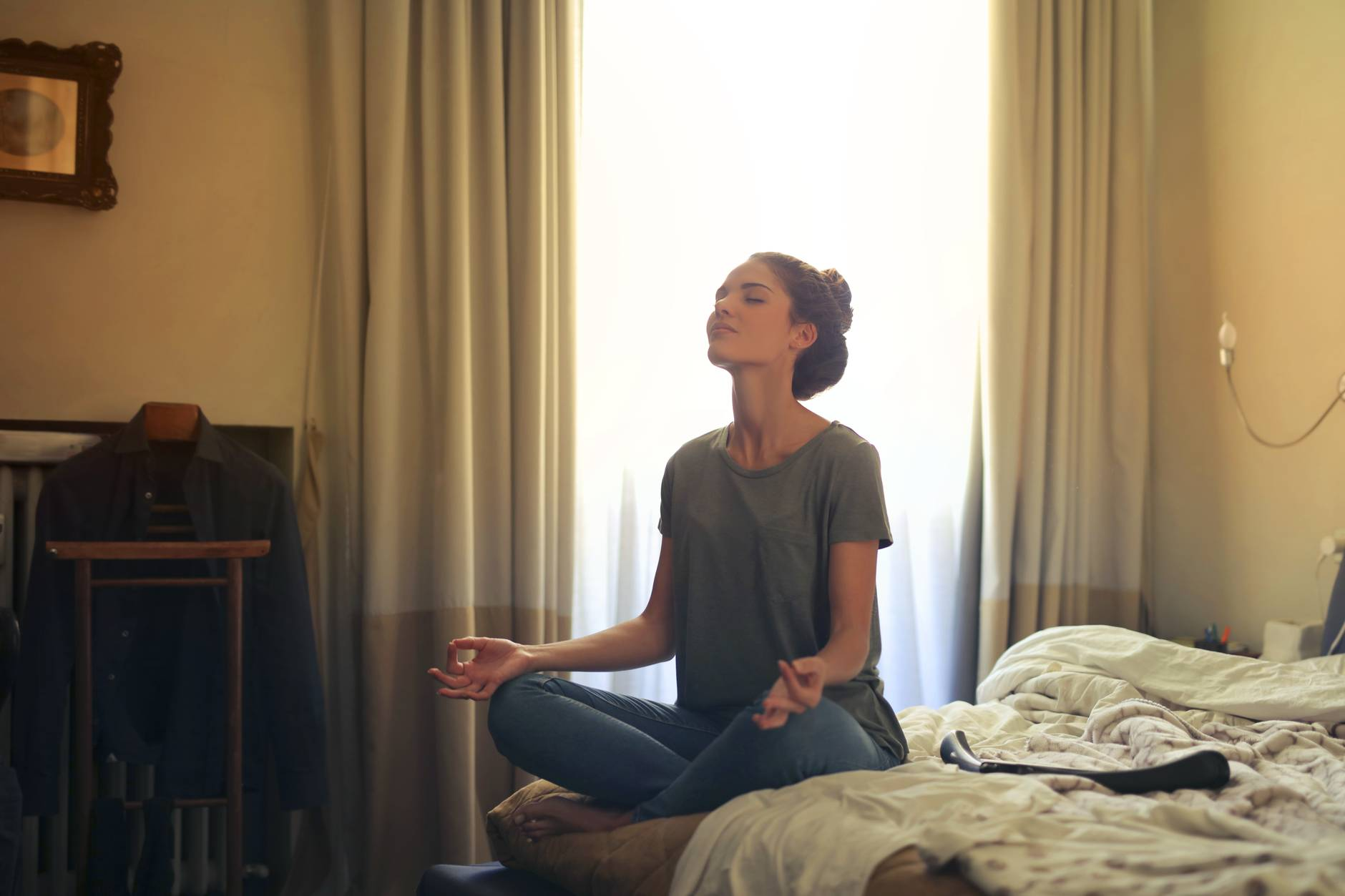 woman meditating in bedroom