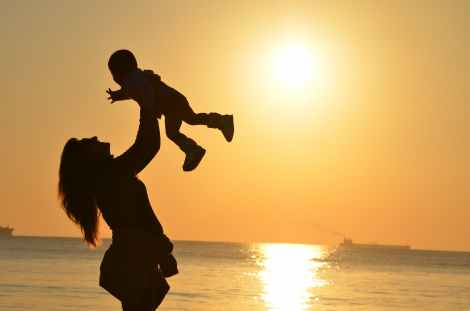 woman carrying baby at beach during sunset, parent wounds, healing your inner child with reparenting