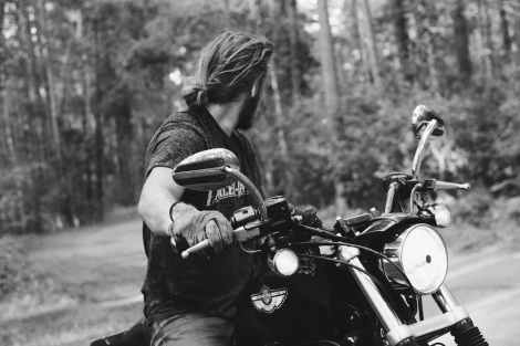 man riding a black motorcycle in gray scale photography