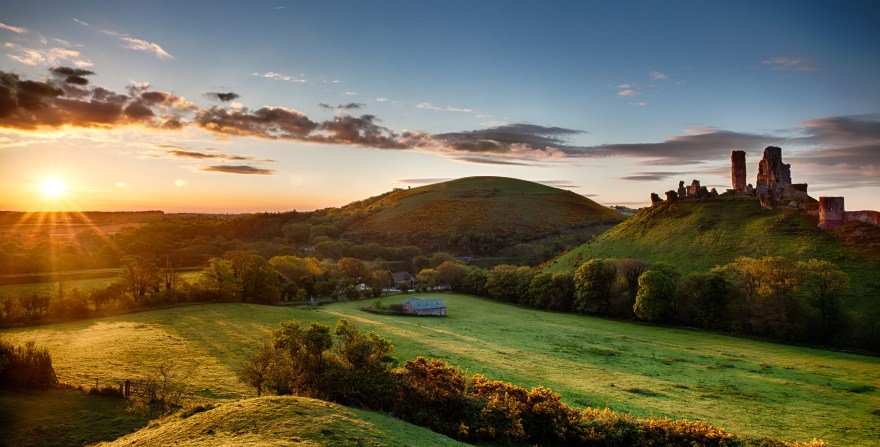 Beautiful sunrise panoramic over Corfe Castle in Dorset England