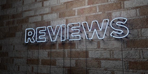 REVIEWS - Glowing Neon Sign on stonework wall