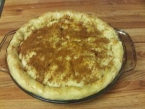 Sprinkling cinnamon and sugar on top of the apple pie.
