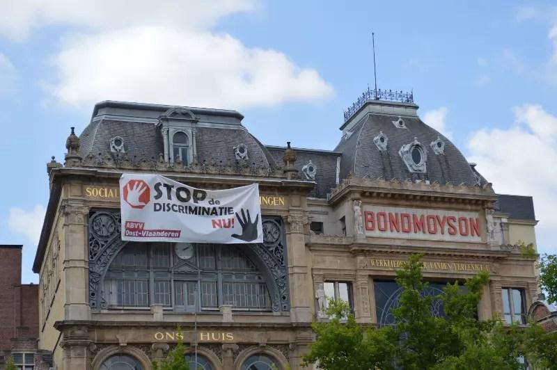 Banner cu încetarea discriminării expus în centrul Gent-ului.