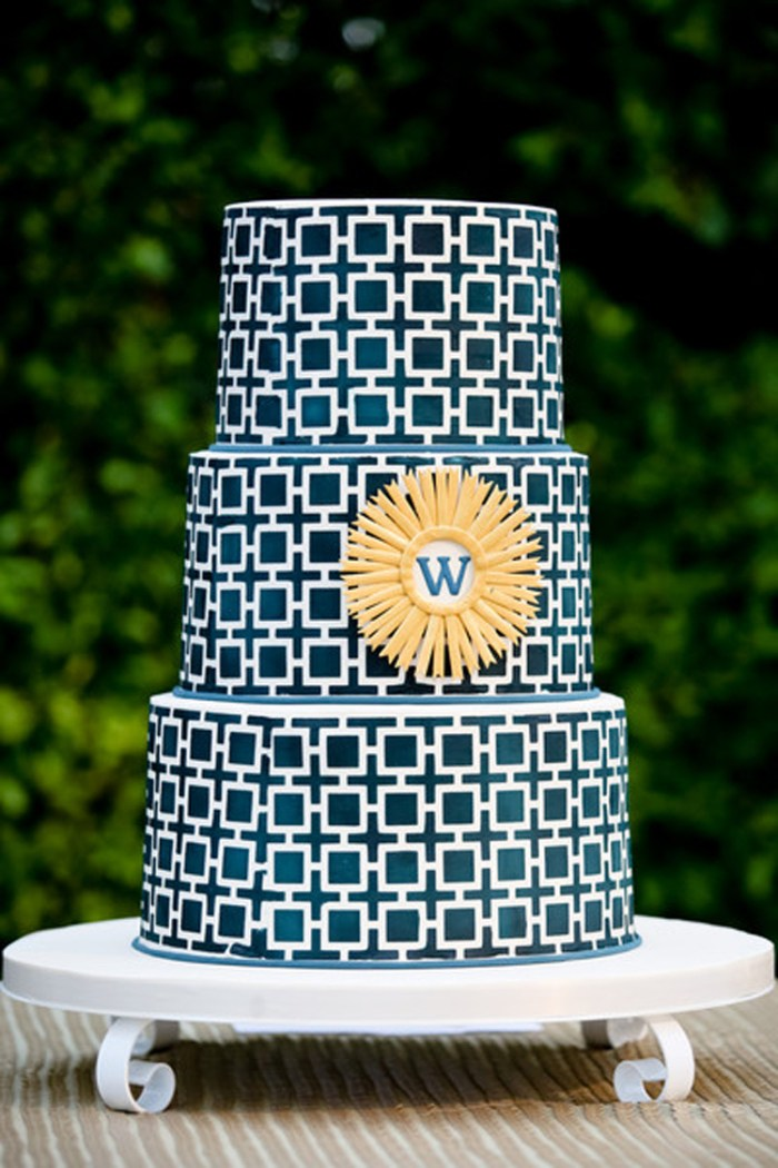 Geometric blue and white wedding cake with yellow new last name initial | See more: http://mysweetengagement.com/15-extraordinary-wedding-cakes-for-all-wedding-styles