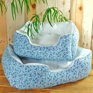Panier pour chats avec de petites fleurs de pissenlits blanches sur fond bleu clair