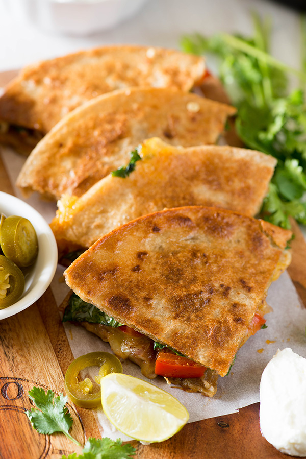 Delicious and healthier Vegetarian Quesadilla recipe made with using multigrain tortillas. Bursting with Mexican flavors, lots of veggies and beans this healthy quesadilla is a perfect recipe to enjoy for any meal.