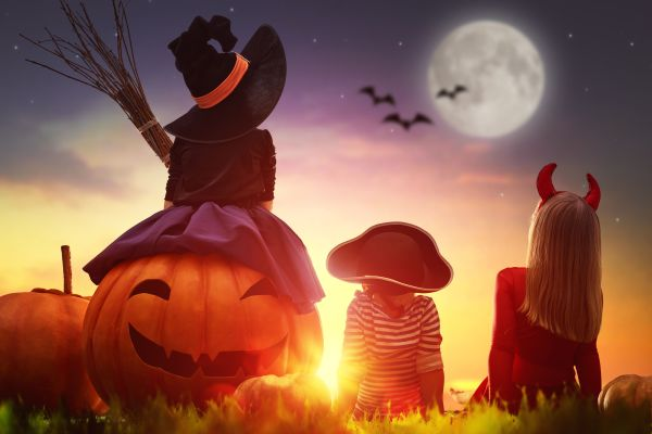 62765538 - happy brother and two sisters on halloween. funny kids in carnival costumes outdoors. cheerful children and pumpkins on sunset background.