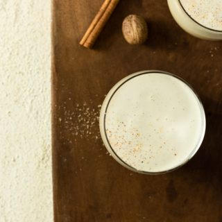 Overhead shot of two glasses of eggnog topped with grated nutmeg and cinnamon on a wood cutting board on a textured off white surface.