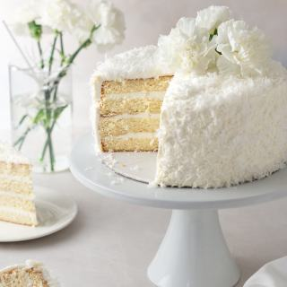 Angled view of a sliced coconut layer cake with Swiss meringue buttercream on a cake stand surrounded by cake slices and a vase of white carnation flowers with a cream colored surface and light textured background.
