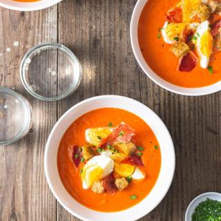 Overhead shot of a Spanish chilled tomato soup, Salmorejo topped with croutons, hard boiled eggs, crispy ham, and chives on a rustic grey wood surface surrounded by multiple bowls of soup, water glasses and a bowl of cut chives.
