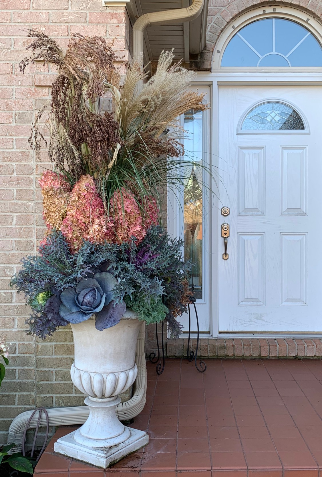 dramatic urn style porch pot with colorful plant materials