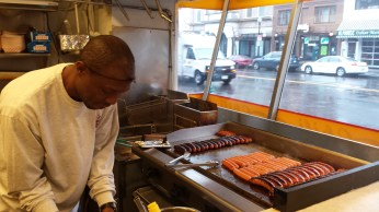 an African-American man grilling sausages on a large grill