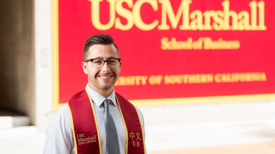 Jack Strauss '19, East Asian language speaker, photographed wearing a dress shirt and tie, with graduation sash, standing in front of a USC Marshall School of Business banner, and smiling into the camera.