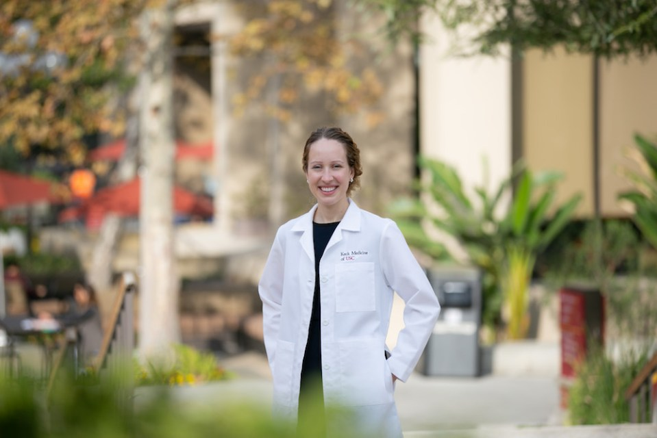 Rachel Lefebvre, MD, Assistant Professor of Clinical Orthopaedic Surgery, photographed standing outside at the Keck facility grounds near the hand center, wearing a white labcoat, she is smiling and looking into the camera with her hands in her pockets.
