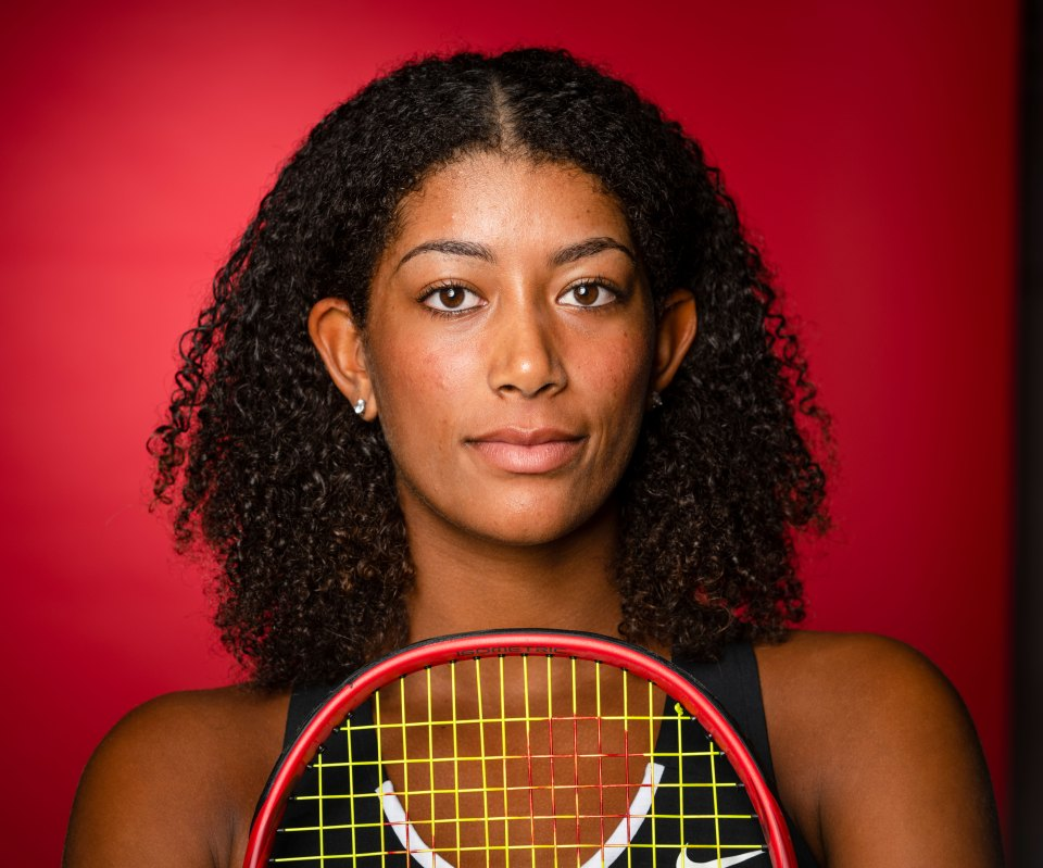 Salma Ewing holding a tennis racket to her chest - she is looking into the camera.