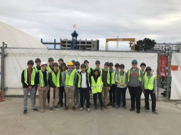 CAIS++ students posing together for a photo at the Boring Company facility.