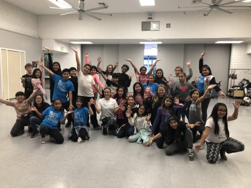 A group children all striking a pose together with Jackie in her dance outreach program.