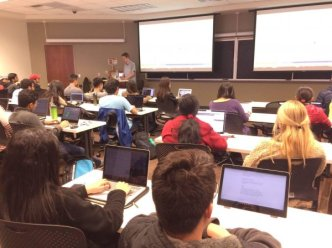 A classroom filled with USC students learning about AI, sitting at desks with computers and listening to the professor.