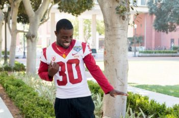 Yoofi Quansah is standing next to a row of trees and wearing his USC uniform.