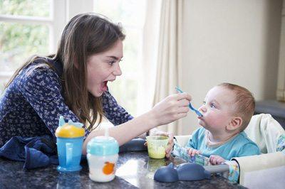 Nanny feeding a baby