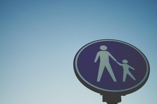 street sign of a parent and child holding hands