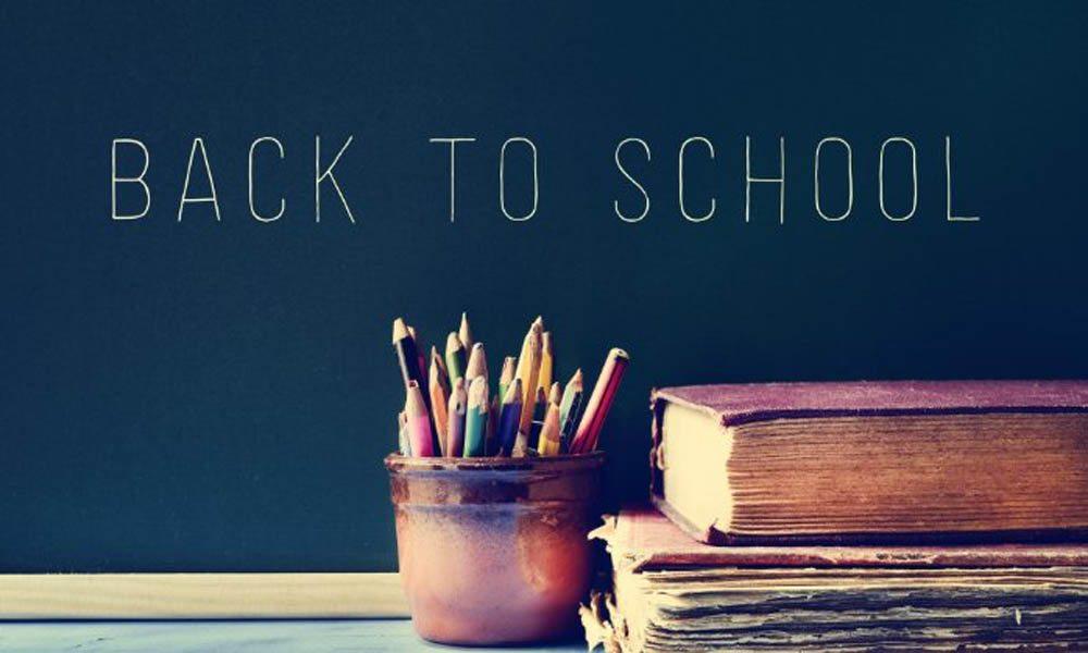 """""""back to school"""" written on a chalk board"""