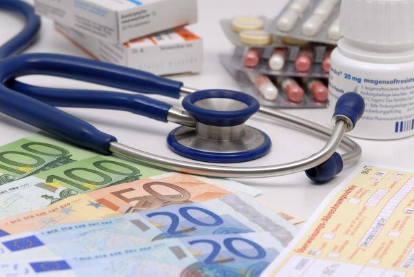 """Themenfoto """"Kosten im Gesundheitswesen"""": Stethoskop mit Medikamenten und Geldscheinen"""