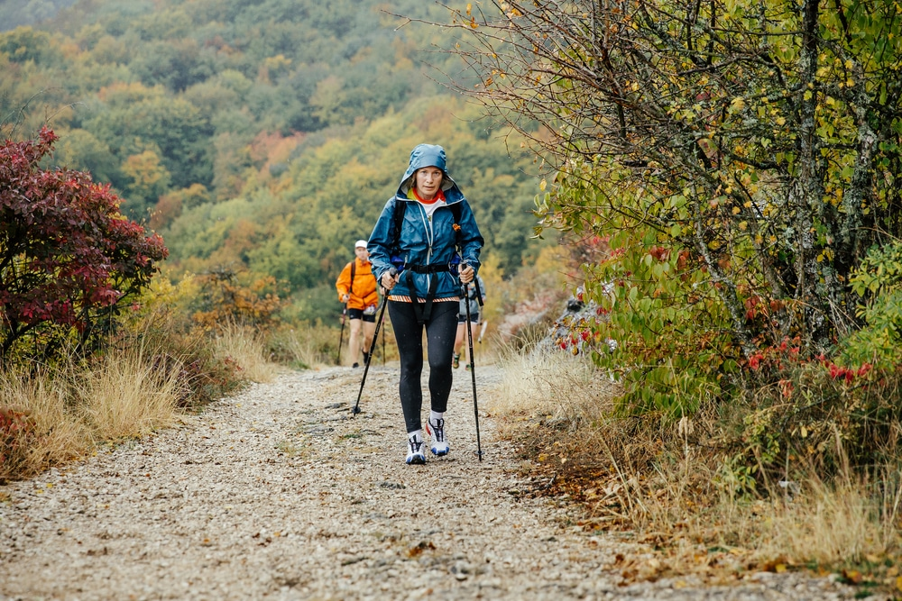 middle aged woman using a nordic walking stick