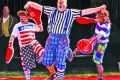 """Above: Clowns play out a slapstick comedy """"boxing"""" ruse during the Carson and Barnes Circus at Lake Lawn Airport on Sunday. At right: A performers twirls hula hoops at the circus. Below: Circus-goers take an elephant ride during the show's intermission."""