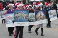 """A group of children march down the center of Elkhorn's North Wisconsin Street displaying artist Jan Castle Reed's Christmas Cards during the 2012 Christmas Card Town Parade. Reed was commissioned for 14 years to paint the Christmas cards, reviving the tradition of artist Cecile Johnson, whose six watercolor paintings for Ford Motor Company in 1958 earned the city it's """"Christmas Card Town"""" title."""