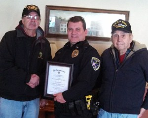 American Legion representatives Paul Rausch (left) and Bob Webster, Sr., (right) presented Village of Sharon Police Chief Brad Buchholz with a Certificate of Commendation Jan. 9.
