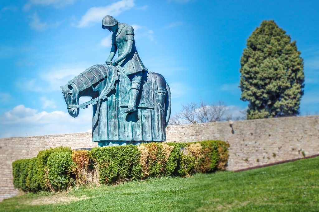 Statue of St. Francis in the lawn of the basilica seen during a day trip to the medieval Umbrian town of Assisi, Italy