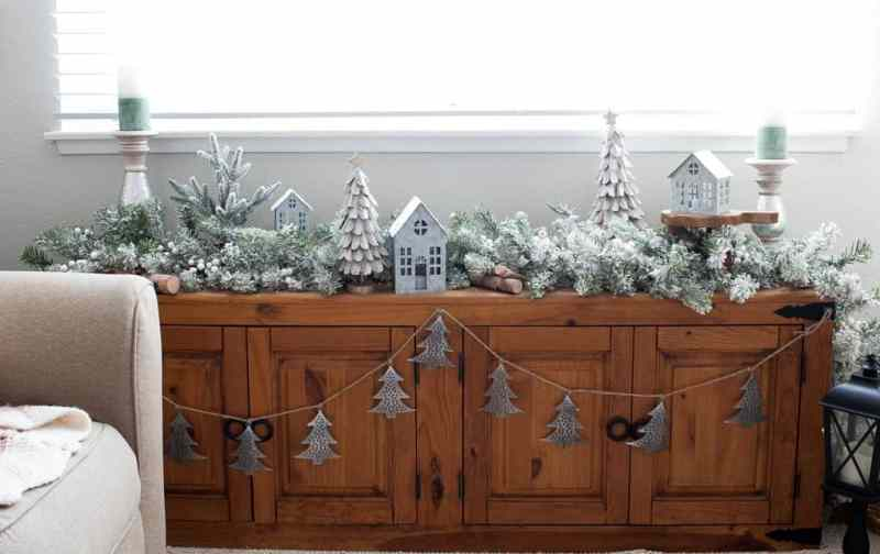 window bench with flocked garland and Christmas decor elements in living room
