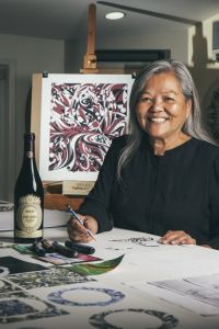 Susan A. Point at her artwork with a bottle of MASI Costasera Amarone