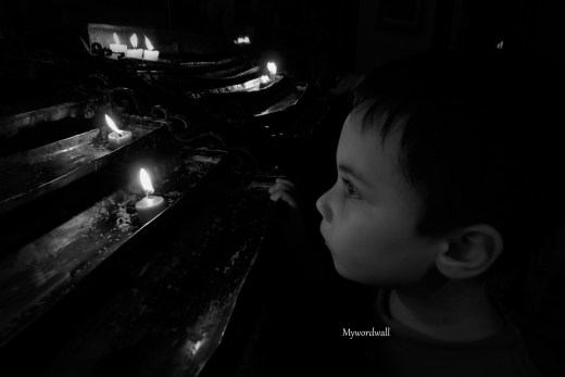 One of my sons lighting a candle inside the San Sebastian Cathedral