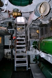 The steps were narrow and steep and brought one to the Torpedo Room. The green things on the walls are torpedos. There are four of them in this submarine.