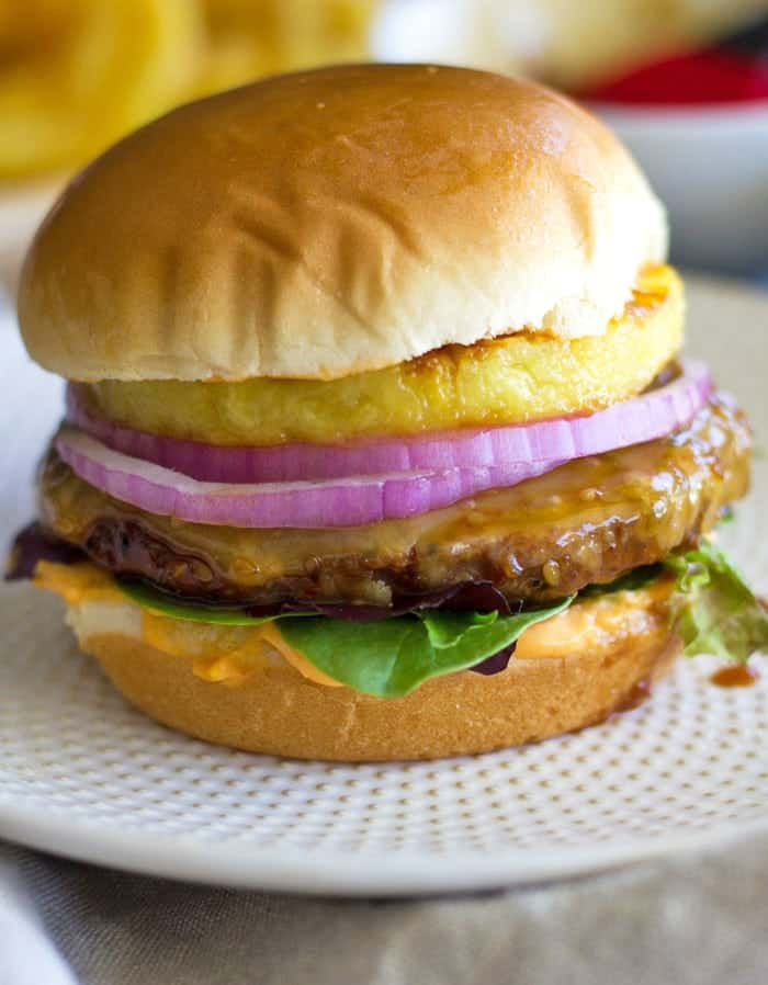 These Spicy Teriyaki Turkey Burgers are the perfect summer BBQ recipe, or a quick and easy weeknight meal featuring grilled pineapple, onion & Sriracha mayo