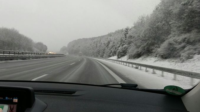 Das Foto zeigt eine verschneite Straße und verschneite Bäume aus der Sicht von einem Cockpit.