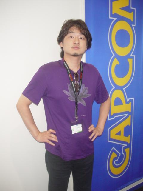Das Bild zeigt einen der drei Grunder von PlatinumGames. Es Zeigt Inaba im Jahre 2004 in Leipzig. Er trägt ein lilanes T-Shirt und eine schwarze Hose. In seinem Kragen steckt eine Sonnenbrille.