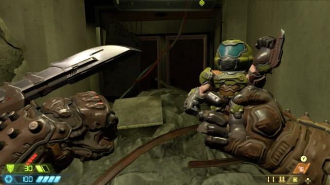 """Auf diesem Bild des Spiels """"Doom Eternal"""" ist eine Hand und eine Puppe in Siegerpose zu sehen."""